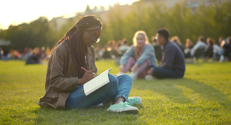 Student practicing a healthy habit by studying outside in nature during her first college semester.