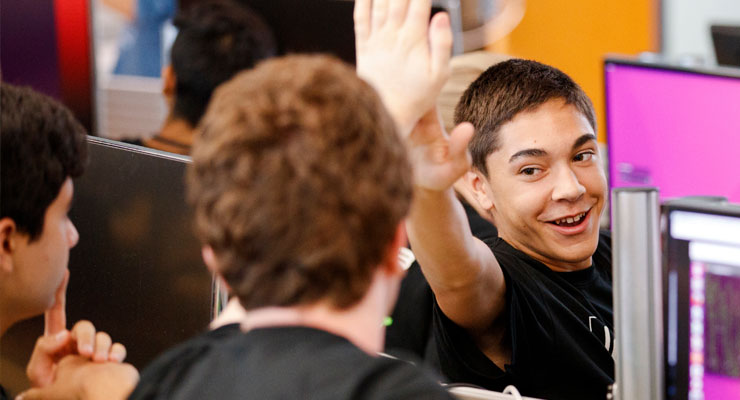 Pre-college students giving a high five.