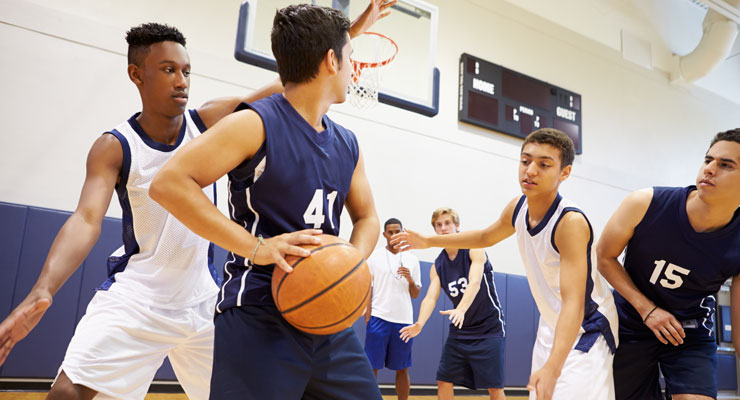 High school students play basketball for their school's team.