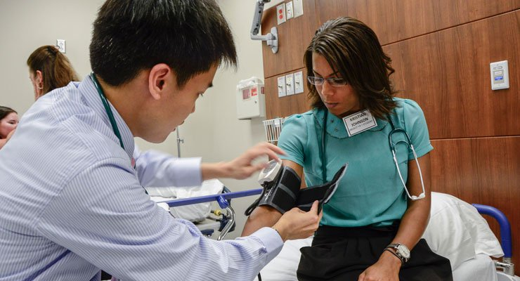 USF students in a medical type major take a person's blood pressure.