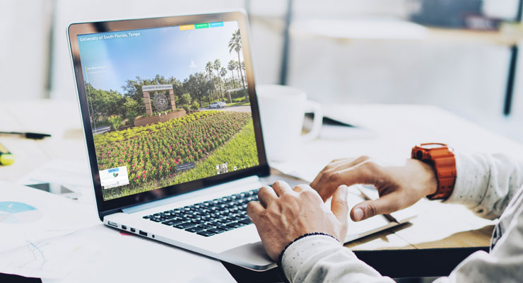 male student on his laptop taking a virtual campus tour