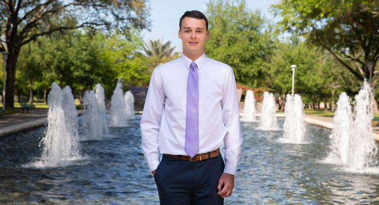 Max, one of the USF National Merit Scholars and son of parent Chris, stands outside of the MLK Plaza on the Tampa campus.