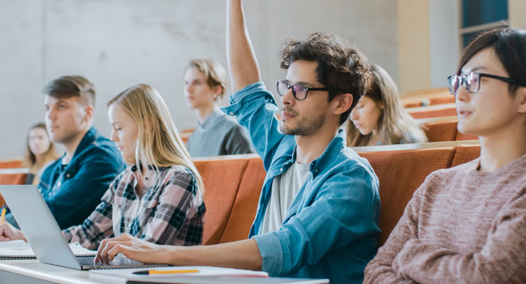 College student raises his hand to ask a question in a college classroom.
