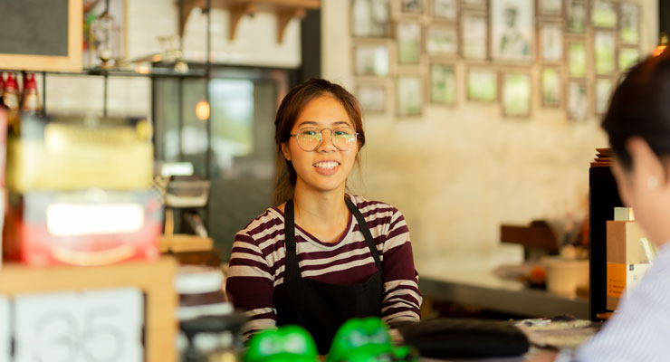Female student working part time at a cafe to improve her college cash flow.