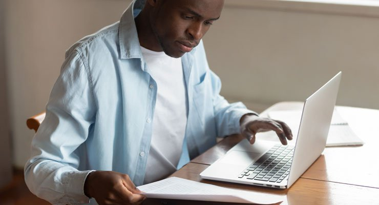 Male student analyzing his expenses on his laptop in order to improve his college cash flow.