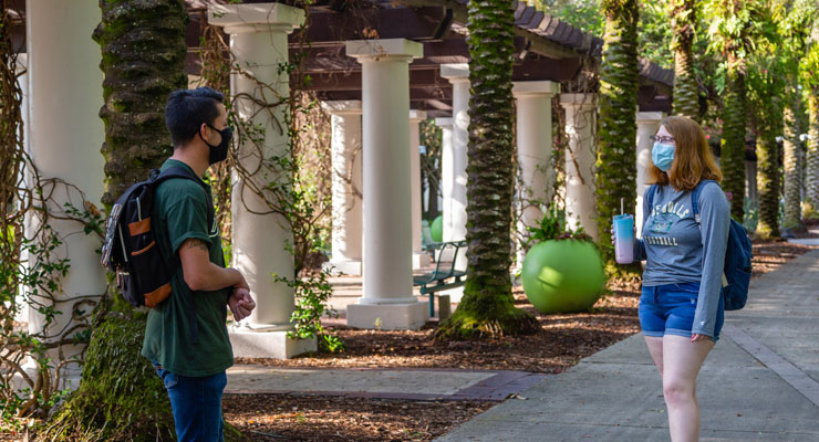 USF students engaging and wearing face masks during covid-19 on campus.