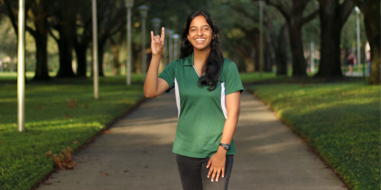 USF female student holding up the bulls sign on campus.
