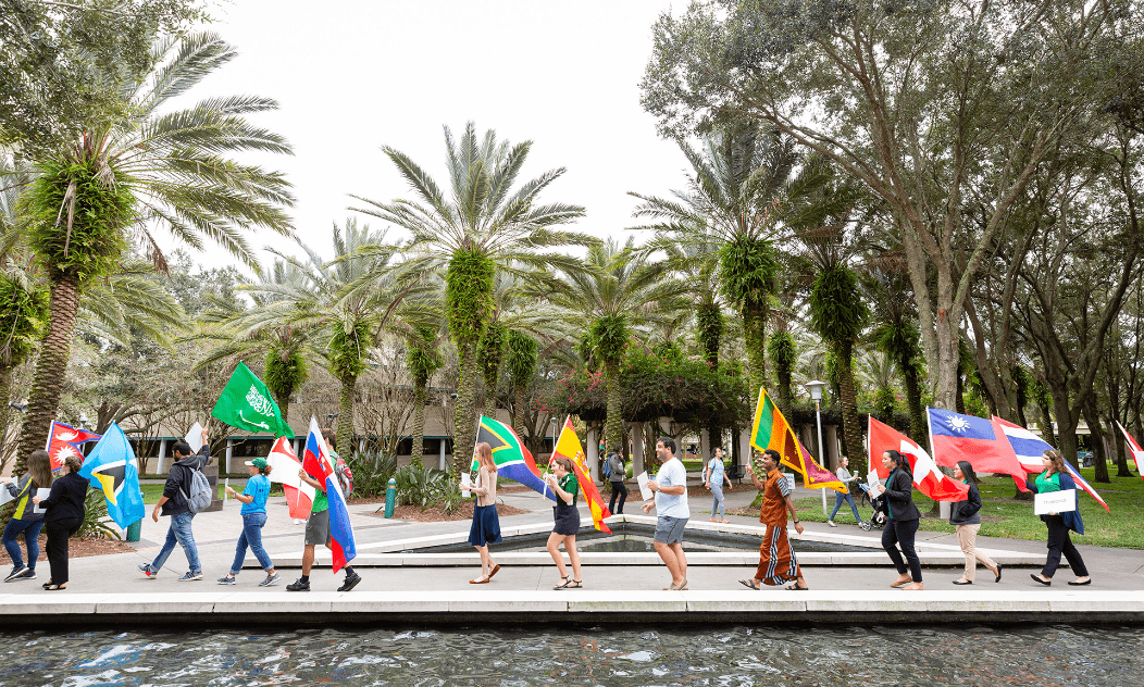 USF students walking together on campus holding up different culture flags for a campus event.