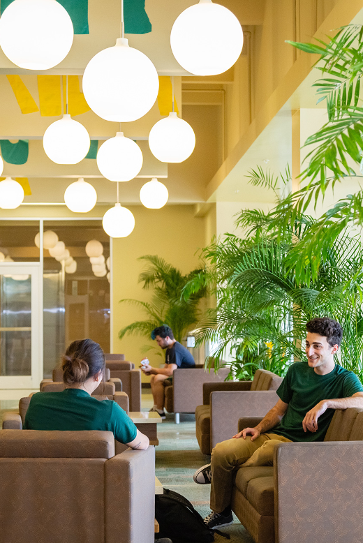 Two USF students talking at a lobby located in one of the resident halls at the Tampa location.