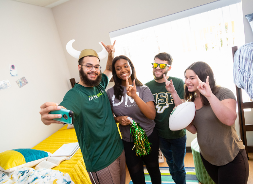 USF students taking a picture together holding up the bulls sign in one of their USF's Tampa Campus apartments.