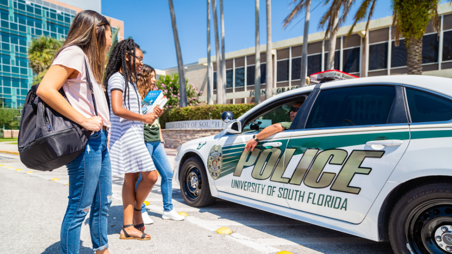 USF students talking with a campus police officer about campus safety.