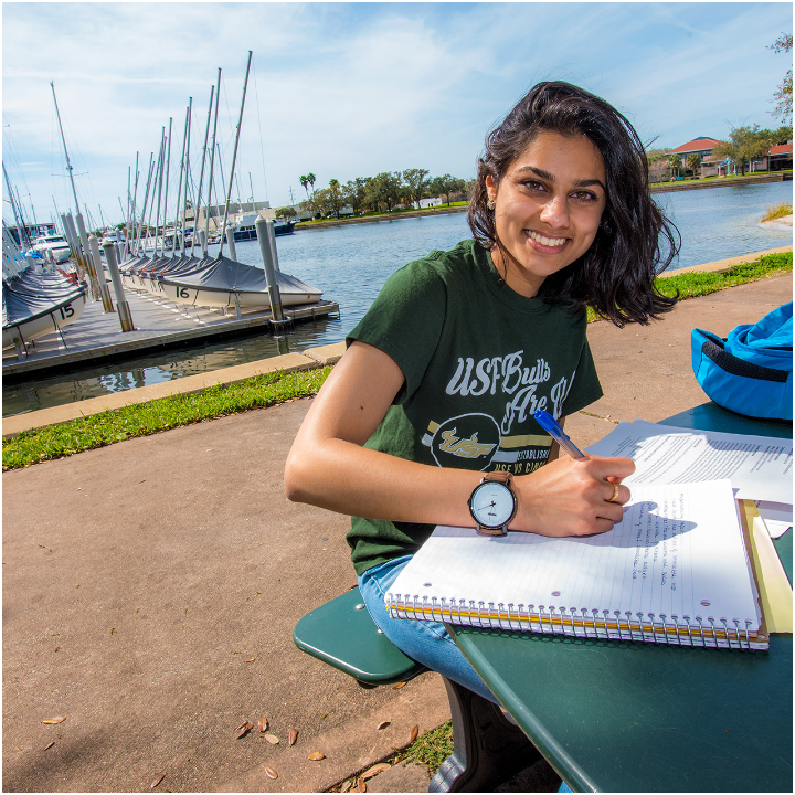 Female student studying and taking notes outside at the USF St. Petersburg campus.
