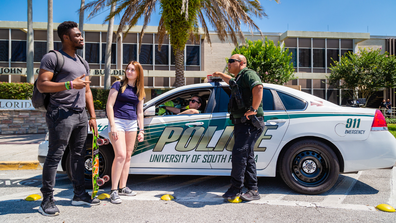 Campus police speaking with a USF student about campus safety outside.