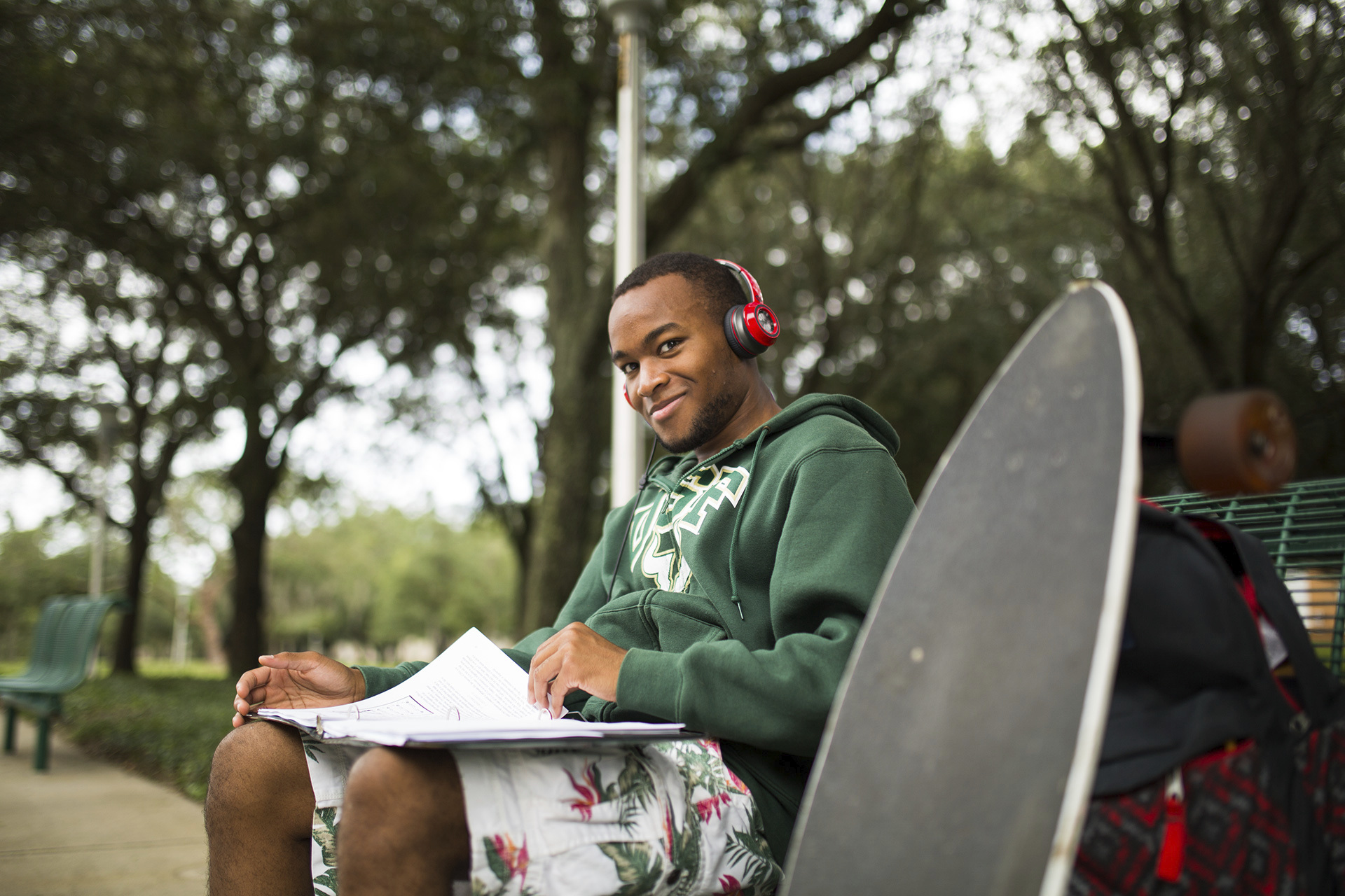 Male USF student researching scholarship opportunities outside on campus.