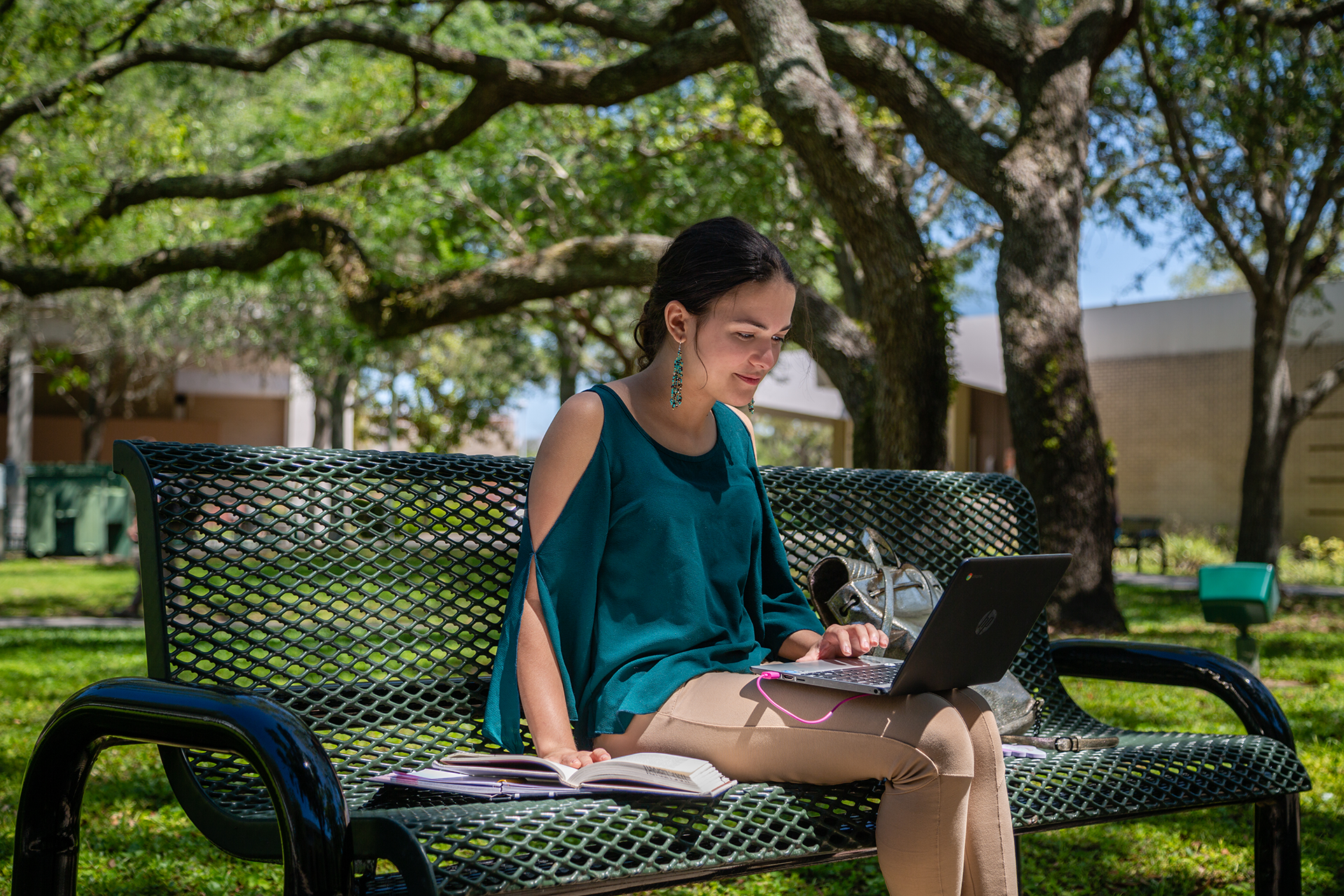 USF student researching USF deadlines on her laptop outside on campus.