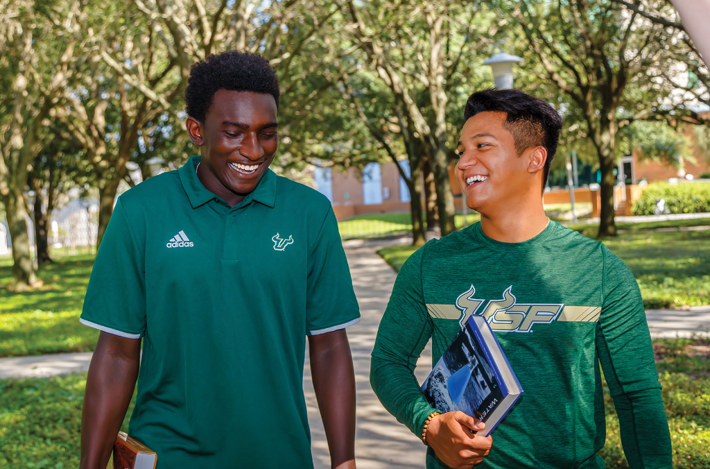 Two male USF students walking on campus discussing admissions scholarships opportunities.