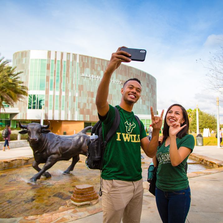 Two USF students taking a picture showing the bull hand sign at USF's Tampa.
