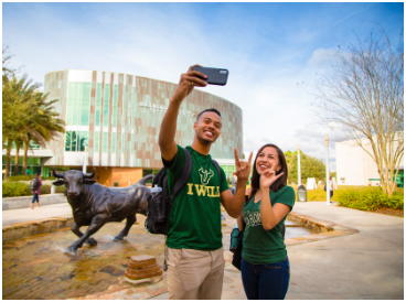 Two USF students taking a picture showing the bull hand sign at USF's Tampa Campus.